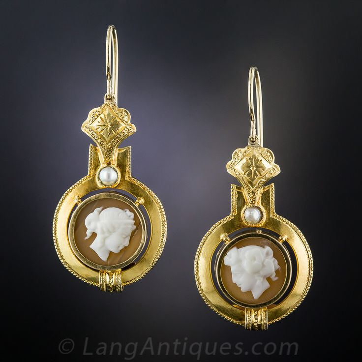 Victorian Cameo Earrings. Sweet and lovely cameo drop earrings dating from the late-19th/early-20th century. A pair of opposing profiles of Classical beauties are hand carved in sea shell and presented in consummate Victorian style, accented with a single half pearl. One cameo has a tiny fissure, thus the beautiful bargain price. 1 1/8 inches, they drop lower from the ear wire.