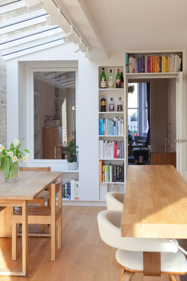 Bespoke joinery for books in this light filled contemporary kitchen. A window seat connects kitchen and living space.