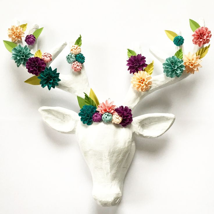 "Transform any space with depth, character and a splash off color by adding a customizable handcrafted paper flower embellished deer head wall mount.  With its uniqueness and attention to detail, this peice is sure to capture the attention of anyone who walks by. Your deer head wall mount will arrive ready to hang with the attached hook and mesaures 12"" L x 14.5"" W.  It is made of paper mache.  Choose up to 5 colors for your flowers by using the standard color chart sho..."
