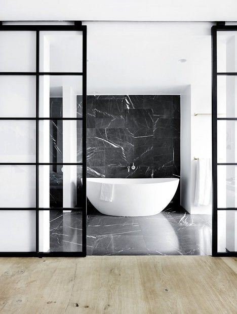 White bath, glass doors, marble wall