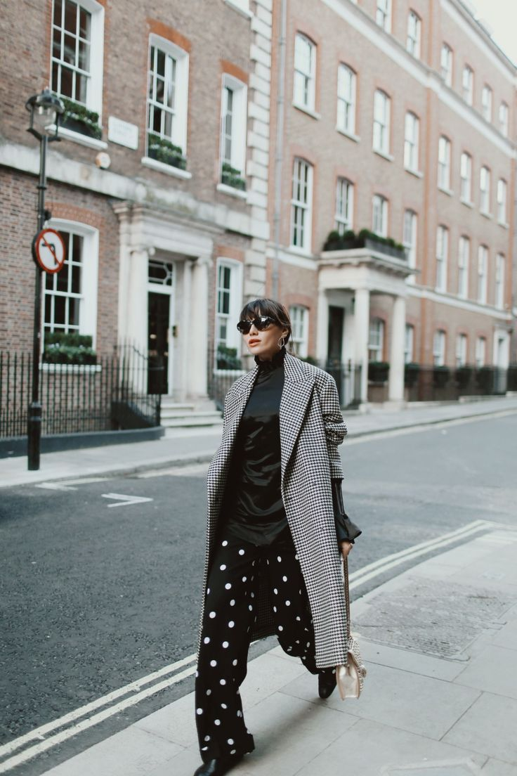 grey coat, black silk turtleneck, and dotted pants