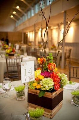 Wooden box centerpieces with curly wilow branches, bells of ireland, orange and yellow dahlias, orange and yellow ranunculas, pink gerbera daisies, orange tulips, green spider mums and mini green hydrangea. ---- This look, but without the curly branches