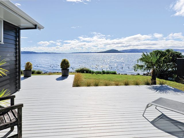 The home opens out onto expansive outdoor decking overlooking the lake.