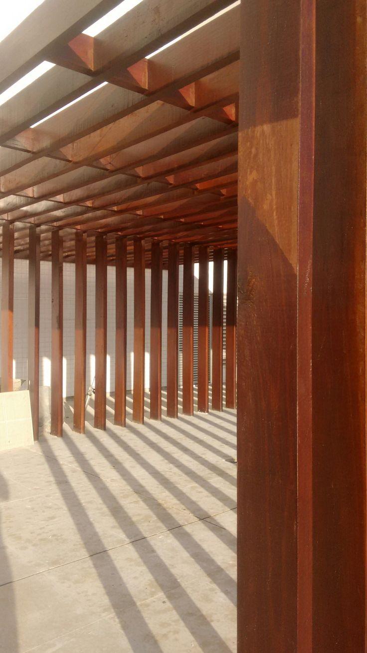 Detalhe de pergolado em prédio residencial, com pilares alinhados às vigas.