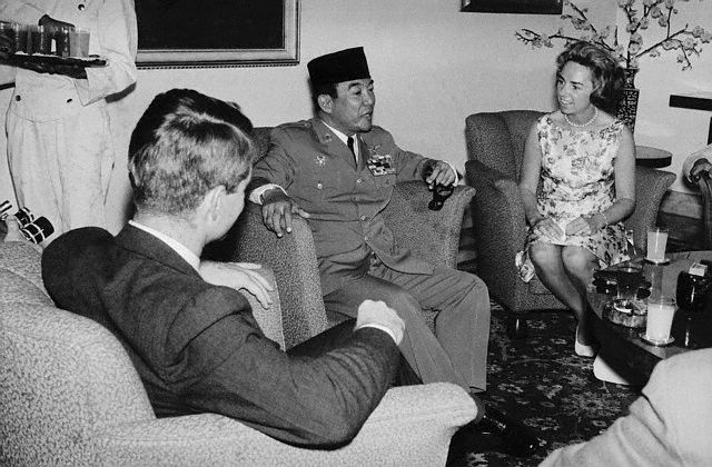 """U. S. Attorney General Robert Kennedy, (L), and his wife visit with Indonesian president Sukarno here. The Kennedy's lunched with Sukarno on this """"courtesy call"""" visit. The president's brother and Sukarno are expected to discuss the Dutch Indonesian dispute and other issues involving Indonesia during informal talks later during the attorney General's six day visit to the island.  Image: © Bettmann/CORBIS  Date Photographed: February 13, 1962"""