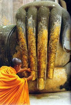 Buddhist monk applying gold leaf to hand of Buddha statue in a temple, Wat Si Chum, Sukhothai, Thailand