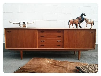"This is a very beautiful and long credenza in great condition. The attention to detail on this piece makes it really special. It has very substantial solid teak conical hand turned legs, sculptural drawer pulls and a rare teak back. This credenza is a show stopper and would take centre stage in any room, Can be used as a hallway console, a traditional sideboard or as a flat screen stand. Compliments modern and vintage decor.  Measures 82"" long x 29"" high x 18"" deep"