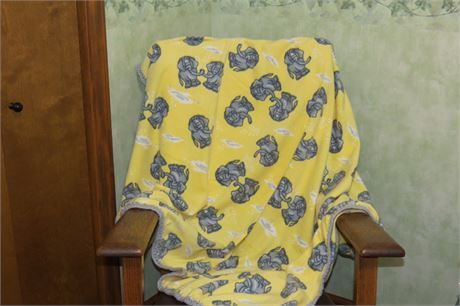 Elephant fleece infant/toddler blanket with crocheted edging.   Slightly larger than crib size this blanket measures 39 inches by 54 inches.   This is fleece with a yellow background with gray elephants - singly and in pairs with trunks raised.   Crocheted edging with gray acrylic yarn.   On the reverse side - the elephants are slightly lighter in color - See the 4th picture - the reverse side is on the left.   The last picture shows the blanket on the back of a queen size sofa.   Machin...