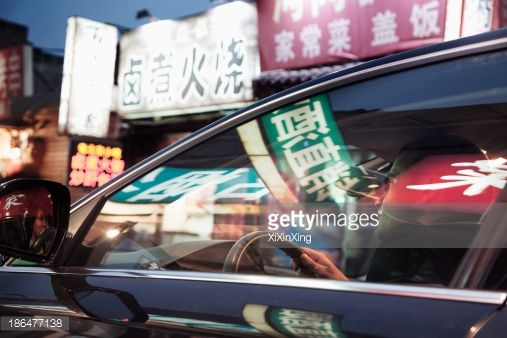 Stock Photo : Young man driving through Beijing at night, illuminated store signs reflected off the windows of the car