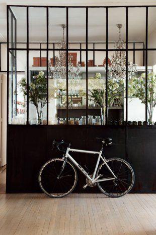 entrée spacieuse avec parquet à fines planches en bois clair et verrière métallique peinte en noir