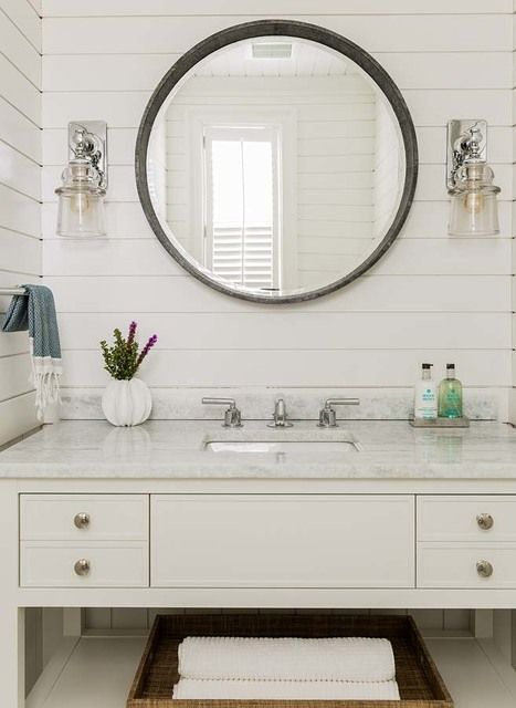 The shiplap covered white walls in the powder room are classic New England coastal style. Completing the space are a large shagreen round mirror and sconces from Waterworks.