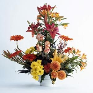 Un centro apasionado y cálido. Elaborado en tonos muy rojos y naranjas, típico del verano. Este centro de flores de verano está compuesto por dalias, gerberas, rosas y lilium | Bourguignon Floristas