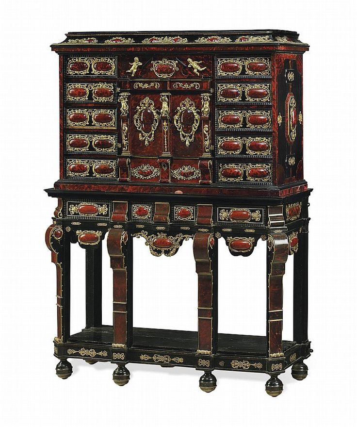 A FLEMISH ORMOLU AND REPOUSSE BRASS-MOUNTED RED STAINED TORTOISESHELL AND EBONY CABINET-ON-STAND<br />ANTWERP, MID-17TH CENTURY, THE STAND RECONSTRUCTED IN THE 19TH CENTURY <br />The cove-molded cornice with applied ormolu and tortoiseshell cabochons above a rectangular case fitted with two banks of fve frieze drawers flanking an architectural center with a drawer and a pair of doors with applied figural pilasters opening to a mirrored inlaid architectural interior, over another drawer, the…