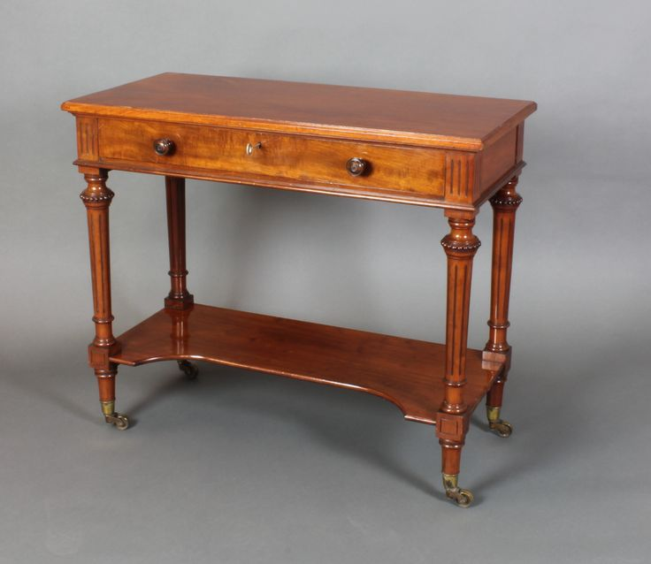 "Lopt 889, A Gillows mahogany side table fitted 1 long drawer, raised on turned and fluted supports with under tier ending in brass caps and castors 29""h x 34""w x 16""d, sold for £520"