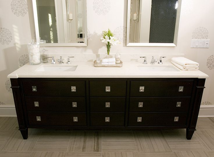 Modern black bathroom design with black bathroom vanity, double sinks, Caesarstone quartz counter top, silver beveled mirrors, polished chrome faucets, ivory cream gray wallpaper and gray tiles floors.