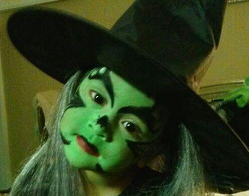 Trucco da strega per Halloween con volto verde e decorazioni a ragnatela