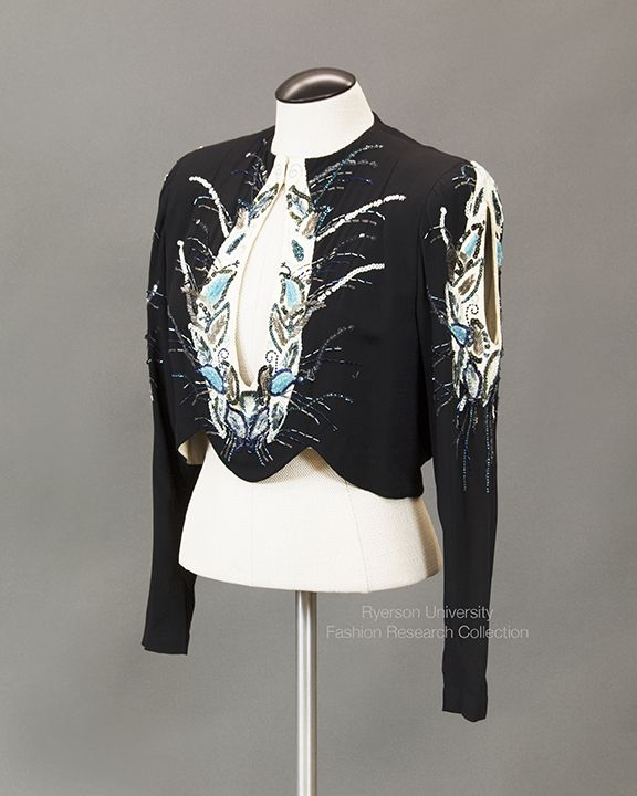 Black silk evening bodice with cream silk cut-outs on bodice and sleeves, padded shoulders and weighted hem. Embellished with blue, gray and silver sequins and beads in leaf motifs on bodice and sleeves. C. 1930s. FRC 1988.02.020