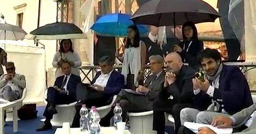"""Uomini seduti che parlano, donne in piedi, sullo sfondo, che reggono ombrelli per proteggerli dalla pioggia (e poi dal sole). L'istantanea arriva da Sulmona, in provincia de L'Aquila, dove sabato 1 luglio era in programma l'iniziativa """"Fonderia Abruzzo"""", due giorni di dibattiti organizzati dalla Regione a cui hanno partecipato, tra gli altri, il governatore PdLuciano …"""