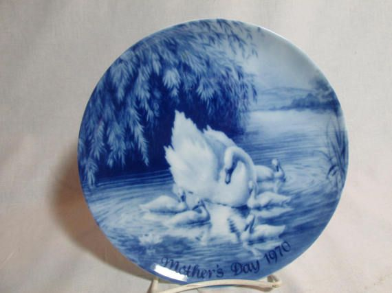 Royale Blue Winter China made the 1970 Mothers Day plate with the mother swan and her 5 young cygnets. The blue and white plate measures 8 in diameter and was made in Germany. The backside of the plate says it First issue of limited edition series. The plate has a pair of holes on the backside for hanging wire. The plate is in excellent condition.