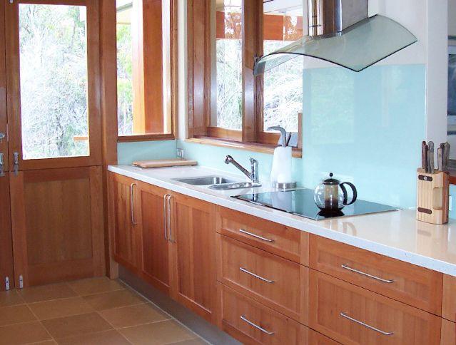 #Kitchen warm timber with green/blue glass splashback, caesar stone bench organic white