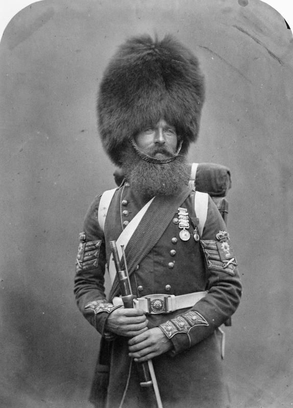 Crimean War, 1854-56: Colour Sergeant William McGregor, Scots Fusilier Guards. He wears genuine bear skin head gear and the sash of his rank. Also carries full pack and rolled-up blanket.