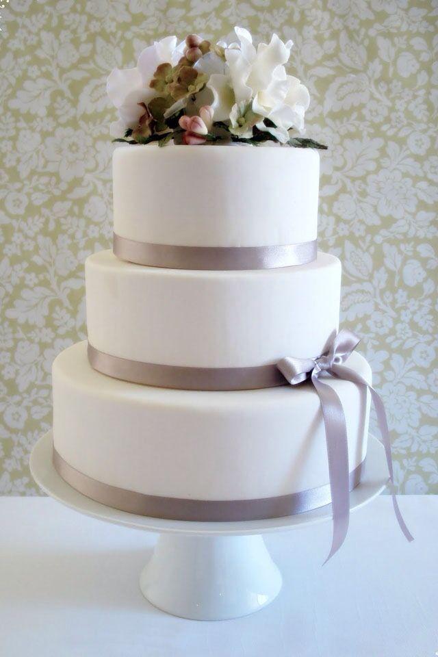 A white wedding cake with grey ribbon