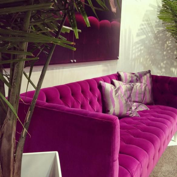 Hot pink velvet tufted sofa in living nook. Palm paper on wall behind