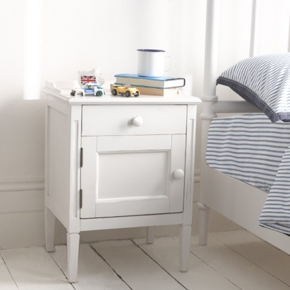 """ASTRID BEDSIDE TABLE We decided on this really versatile bedside table as it goes effortlessly with so many wooden or upholstered beds. Painted in a nice off-white and then applied with a """"dirty wax"""", it has an adjustable door which can open both to the left and right."""