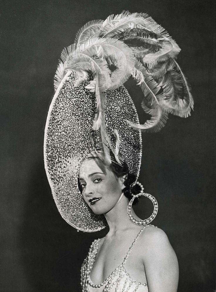 Dames hoeden. Mode uit Londen. Revue. Portret van een model met een grote hoed met struisvogelveren en parels, welke te zien is in de cabaretshow 'Magic Nights', geproduceerd door de heer Cochran. Engeland, april 1932.