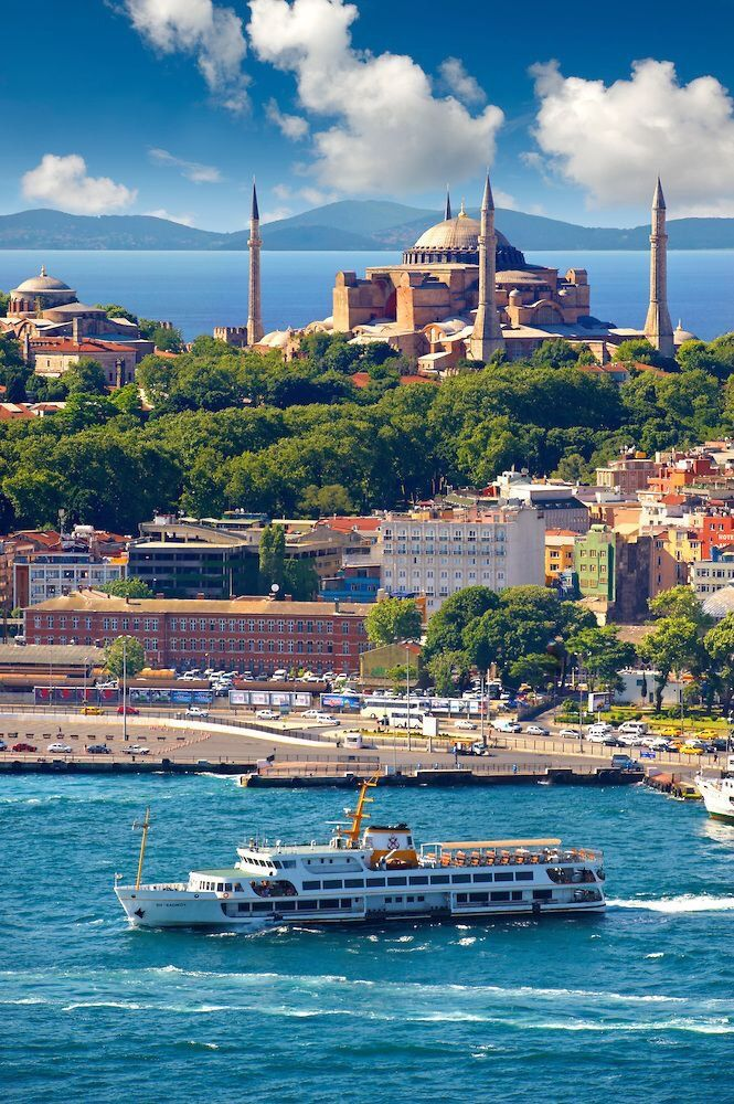 The exterior of the 6th century Byzantine (Eastern Roman) Hagia Sophia ( Ayasofya ) on Sarayburnu or Seraglio Point with a ferry and the banks of the Golden Horn in the foreground, Istanbul Turkey. Check @nowyefendihotel for accomodation www.boutiquesmallhotels.com/efendi-hotel
