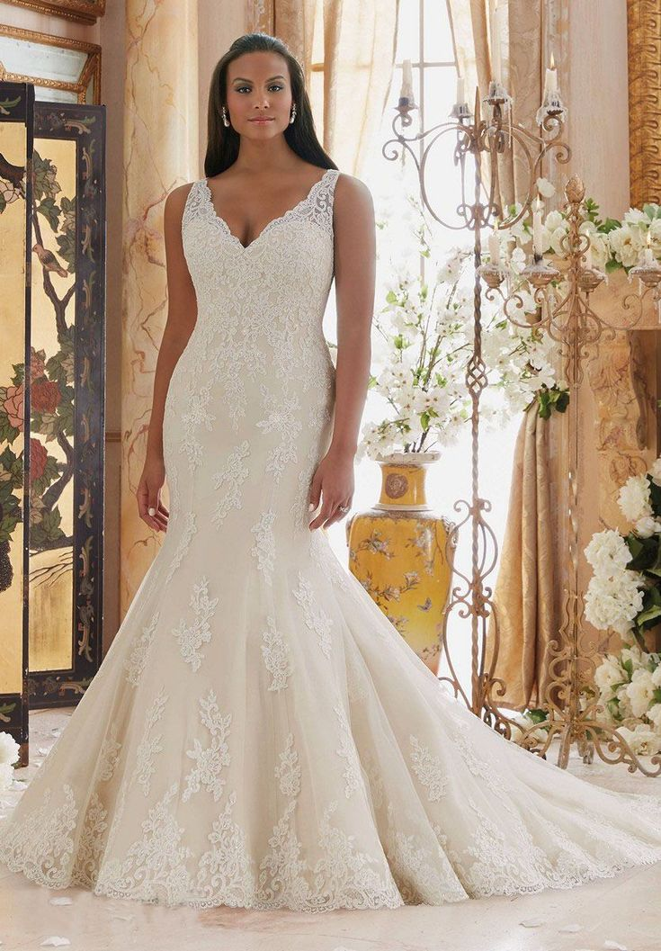 A scalloped illusion V-neckline tops the sleeveless sweetheart bodice of this Mori Lee Julietta 3202 plus size wedding dress with trumpet silhouette. This gown with chapel train is styled in subtly beaded embroidered lace appliques on tulle. Shoulder straps lead into the illusion back accented with covered buttons and the skirt flows from the dropped waistline and showcases a scalloped hemline.