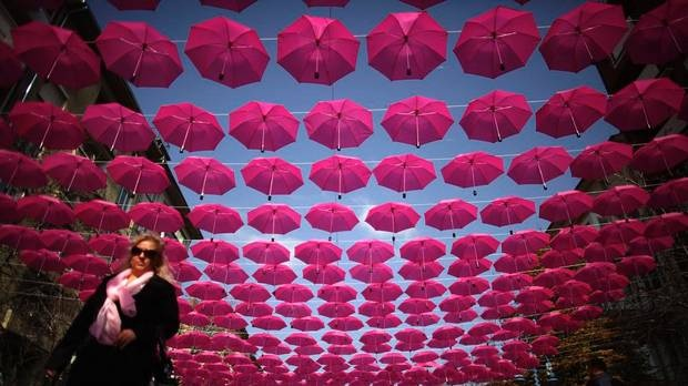 A woman walks under a canopy of pink umbrellas on a street in downtown Sofia, Bulgaria. The art installation, that includes up to four hundred umbrellas, is part of a campaign aiming at awareness, prevention and treatment of breast cancer.