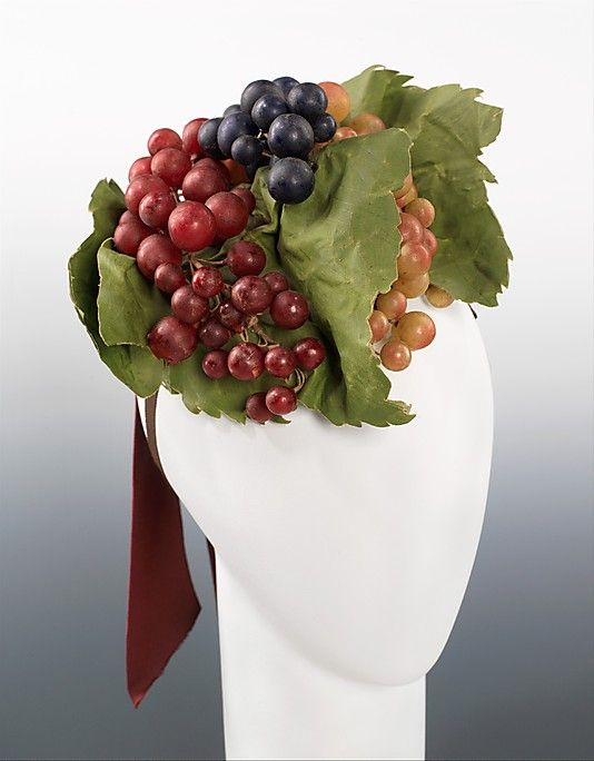 Elsa Schiaparelli Cocktail Hat Circa from Fall 1939 collection features bunches of various types of grapes perched on top of the wearer's head. The idea itself of wearing fruit on one's head is humorous and whimsical but also surreal in that although the fruit and the surrounding leaves are extremely realistic, the hat is a chic, functional accessory.