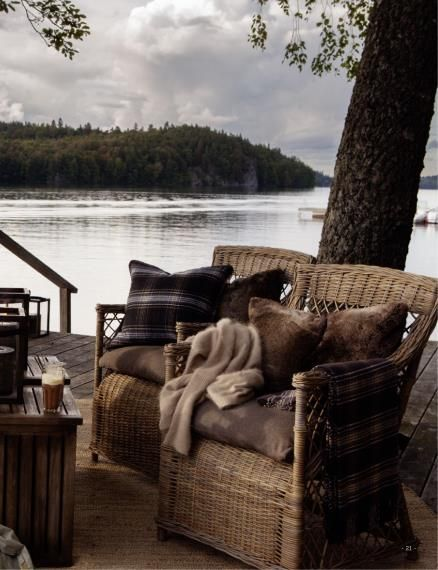 """These chairs almost seem to say """"let's sit and watch the sunset together"""". I love how they draw the comfort of a cottage out towards the cool lake."""