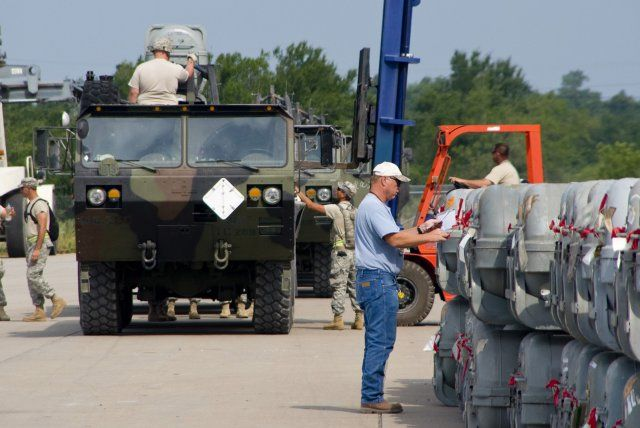 Soldiers from the 261st Ordnance Company and civilians from McAlester Army Ammunition Plant, Oklahoma, load missiles onto flatbed trailers during Operation Golden Cargo in June 2011.