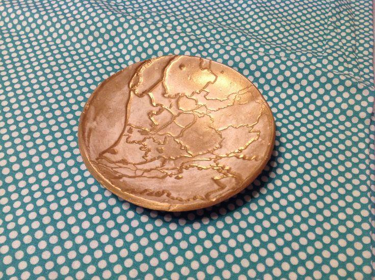 Kommetje, zelf gemaakt van klei met daarin een stempel van Nederland. Later geverfd met goudverf en een laagje mod podge ter bescherming.  Bowl made of clay stamped and painted gold.