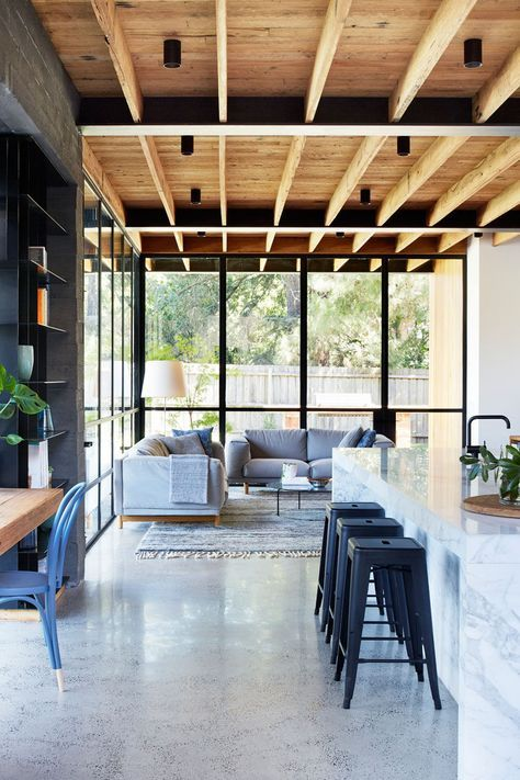 The interior of this modern house extension features materials that will age and patina over time, creating a sense of warmth. An exposed recycled wood ceiling runs the length of the living room and kitchen.