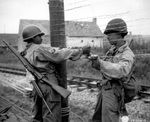 US Army African-American soldiers T/5 Dexter Clayton and M/Sgt. Nelson T. Ewing tying wire to form a fence, France, 25 Jul 1944; note Springfield M1903 rifle and M1 Carbine (partially hidden)