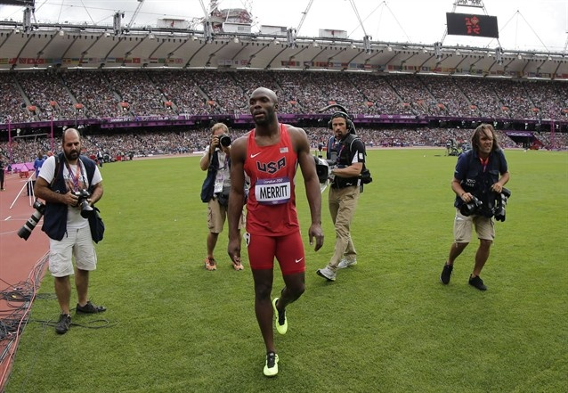 United States' LaShawn Merritt, center, walks in the infield after pulling out with an injury from a men's 400-meter heat.