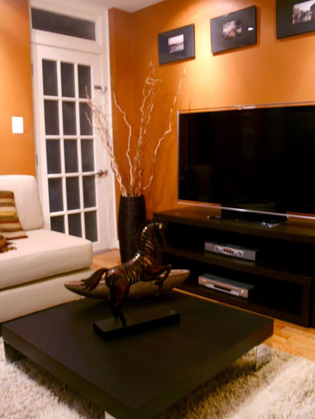 Orange walls with brown & tan furniture & hardwood floors.. Love it! All it needs is a stone fireplace.