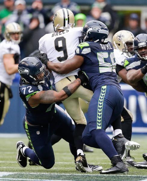 Seattle Seahawks defensive end Michael Bennett (72) and defensive end Cliff Avril (56) sack New Orleans Saints quarterback Drew Brees (9). (Elaine Thompson/AP)