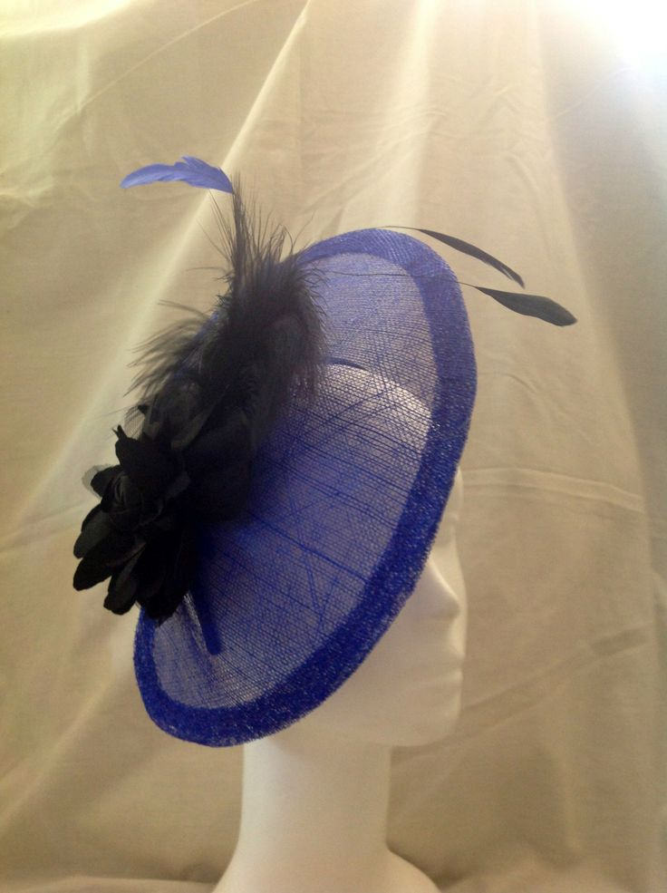 The Antonia is a large fascinator on a black head band the centre piece is a large black flower surrounded by a half moon shaped sapphire sinamay base with matching feathers. $130 AUD.
