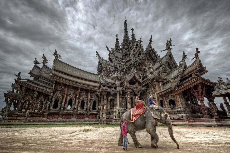 Tourists riding an elephant in front of Wang Boran/Prasat Mai (The Sanctuary of Truth) in Pattaya, Thailand.