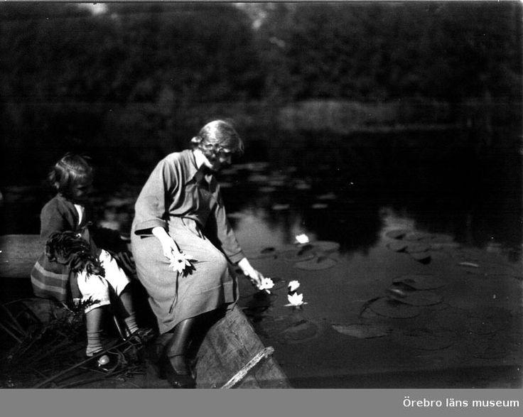 Två flickor i en båt plockar näckrosor i Marksjön, Örebro.  Ca 1920-tal. Foto: Samuel Lindskog