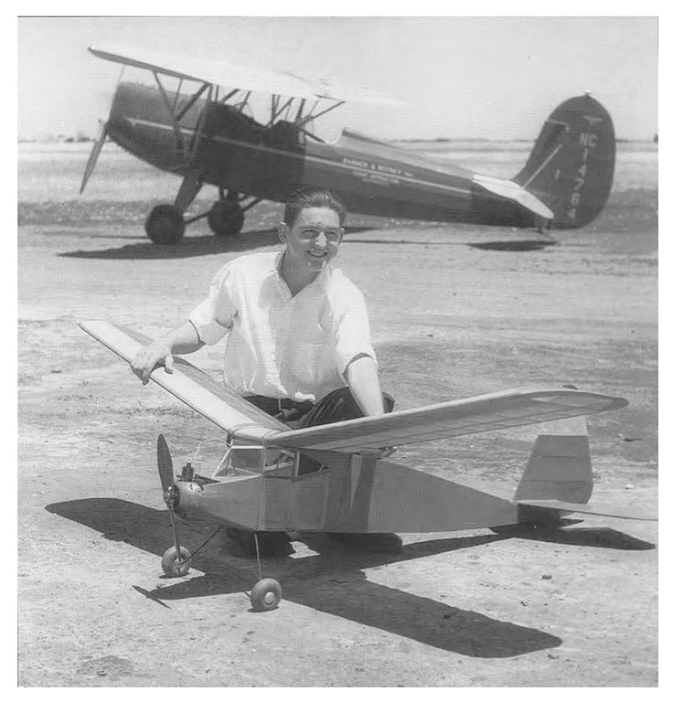"""Nick Sanford in 1937 with his original design """"Sac-Tex""""powered by a Brown Jr. at the Sacramento Airport for a State Fair Texaco event. The model had a 7 1/2 foot wing with a 12 in. chord and a Clark-Y top and RAF32 bottom airfoil. The full size Fairchild 22 in the background is a rare one with a Gipsy 90 H.P. engine"""