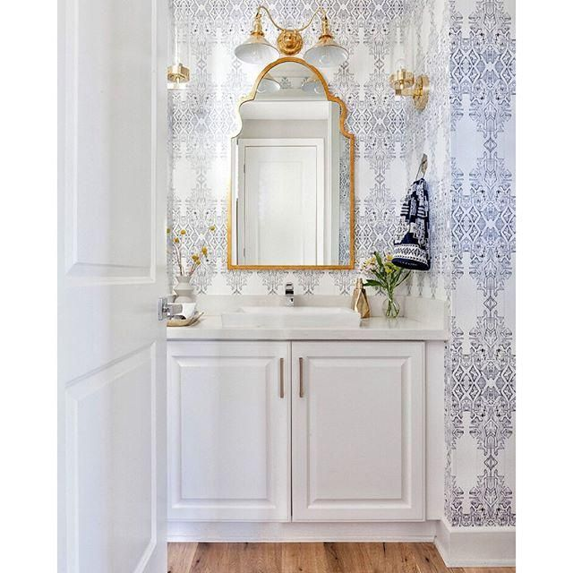 Love this gorgeous blue and white printed wallpaper in this sweet guest bathroom. Love the white millwork on the cabinets and the bright brass accents, fixtures and hardware!