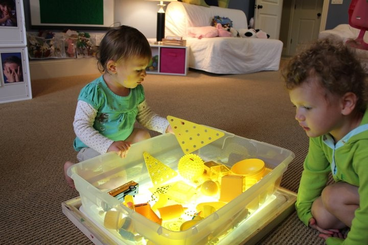 For Infants and Toddlers - clear plastic sensory container on top of the light table.