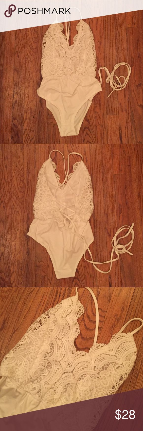 White lace bodysuit NWOT. Never worn only tried on. Supper cute open back one piece. Feels like it can be worn as a bathing suit but I'm not positive. I bought it to go with high waisted shorts but it didn't fit me quite right :/ supper long strings so you and do the back however you want or even as a halter Tops