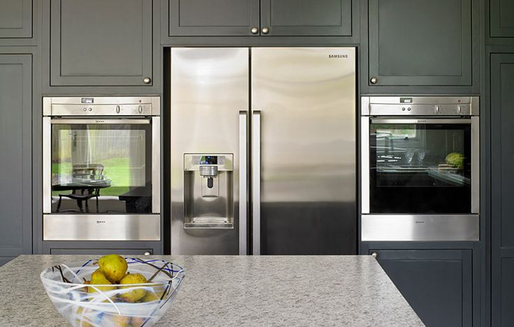 Built in appliances, grey blue fitted kitchen cabinets, granite worktops. Esher kitchen.
