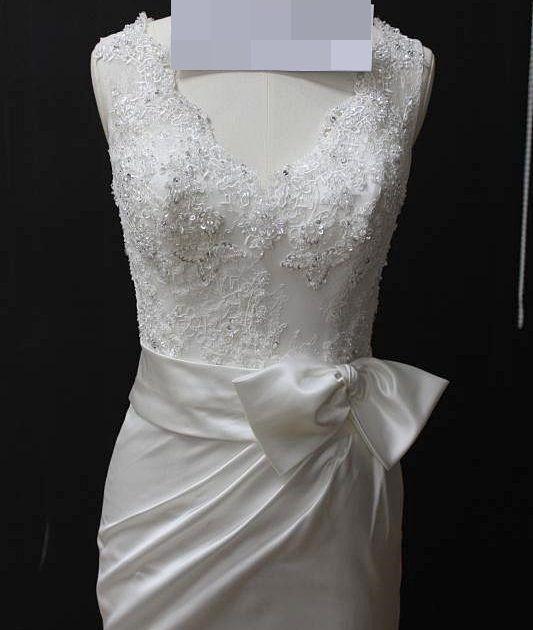 Vestido de noiva sereia, bordado no corpete, gola em V, laço na lateral do quadril e no começo da calda, costas com transparência. Via Brasil Noivas.